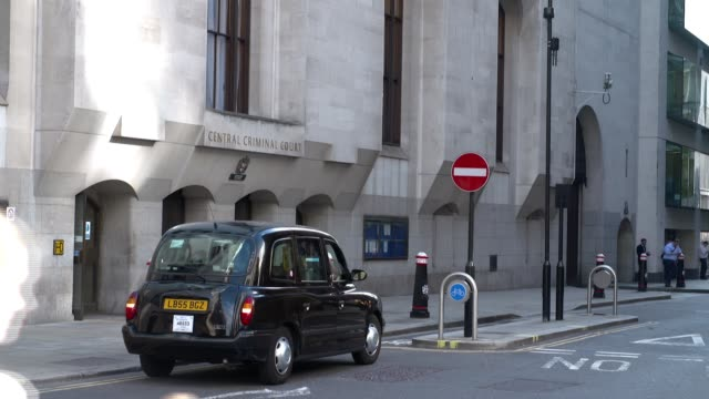 london the old bailey ext taxi outside central criminal court entrance tilt up windows / domed roof / statue carvings tilt up lady justice statue on... - オールドベイリー点の映像素材/bロール