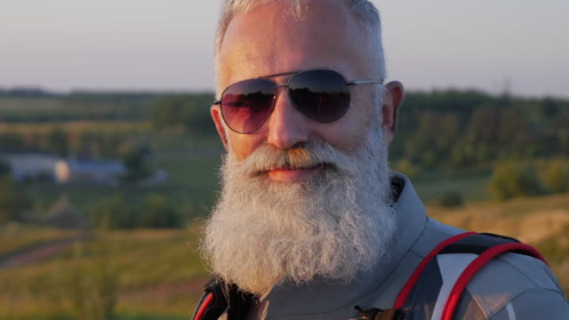 old bearded biker looks at nature - beard stock videos & royalty-free footage