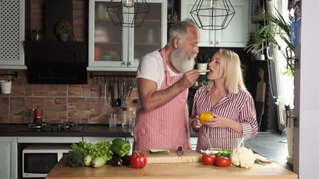 old bearded man and young woman are preparing salad in the kitchen. two persons - facial hair stock videos & royalty-free footage