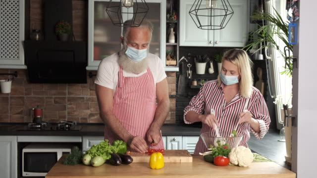 old bearded man and young woman in masks are preparing salad in the kitchen. two persons - meal stock videos & royalty-free footage