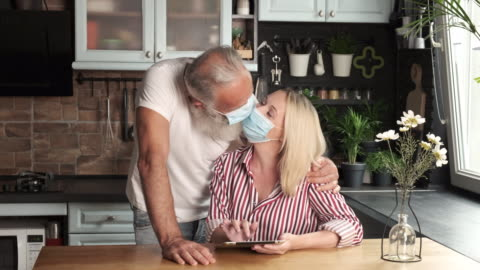 old bearded man and young woman in masks kiss. two people - kissing stock videos & royalty-free footage