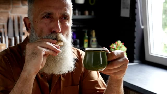 old bearded man drinking coffee and eating cookies in the kitchen - mature men stock videos & royalty-free footage