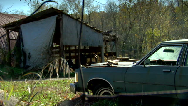 old beat up car parked in front of old beat up looking shack trees bg rundown broken down poor rural country - lincoln town car stock videos and b-roll footage