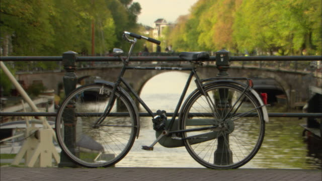ws old bicycle parked by canal, amsterdam, netherlands - canal stock videos & royalty-free footage