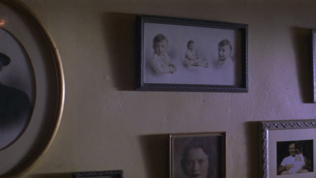 Old black and white family photos adorn a wall.