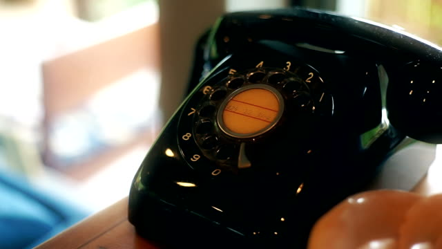 old black fashioned telephone on a table. - linea telefonica video stock e b–roll