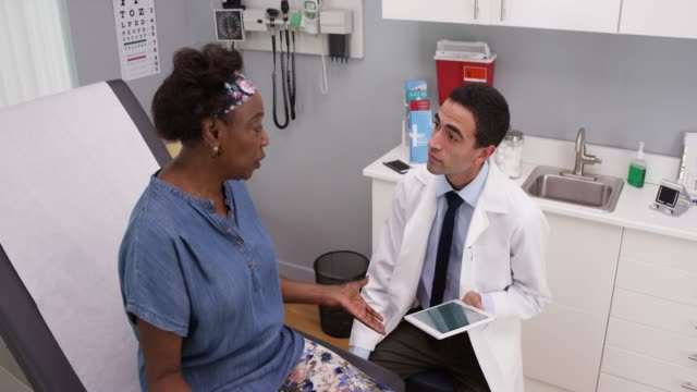 Old black woman explaining health issue to young male hispanic doctor in office