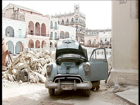 Old blue 1950's car being repaired door and bonnet open alongside pile of rubble with square and old buildings in background; Havana