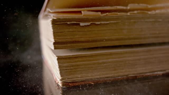vídeos de stock, filmes e b-roll de slo mo ld livro antigo caindo sobre a superfície negra - old book