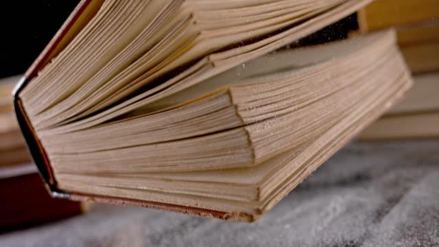 vídeos de stock, filmes e b-roll de slo mo velho livro aterrissando em uma mesa empoeirada - old book