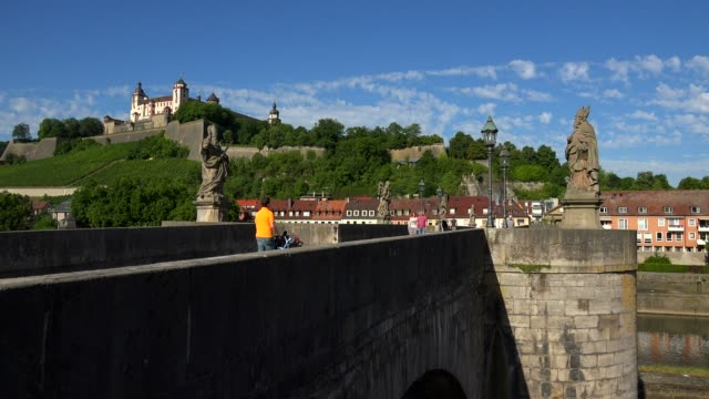 vídeos de stock, filmes e b-roll de old bridge across river main with marienberg fortress, wuerzburg, lower franconia, bavaria, germany - plano americano