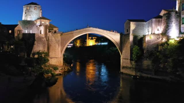 夜のモスタルの空中古い橋とモスク - ボスニア・ヘルツェゴビナ点の映像素材/bロール