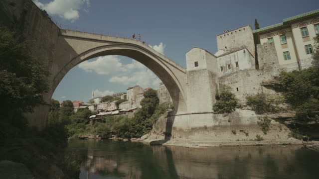 old bridge in mostar, bosnia and herzegovina. view of bridge and old city during the day in summer, - bosnia and hercegovina stock videos & royalty-free footage