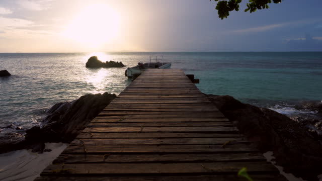 old bridge wood on the beach and beautiful sunset at the island. - terrazza in legno video stock e b–roll