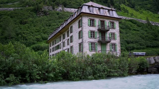 old building near the river in swiss alps - stone house stock videos & royalty-free footage