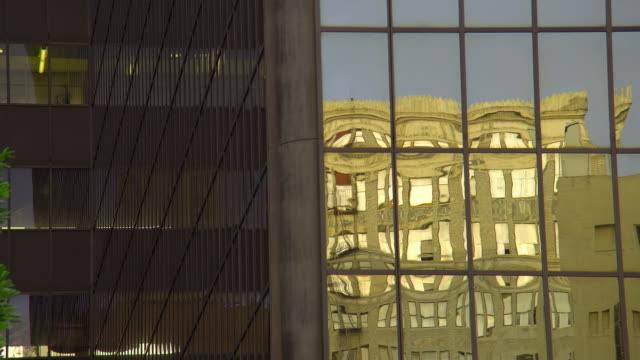 cu, old building reflected in modern building, los angeles, california, usa - campo totale video stock e b–roll