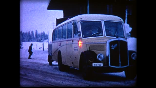 1969 old bus plowing through snowy mountain road