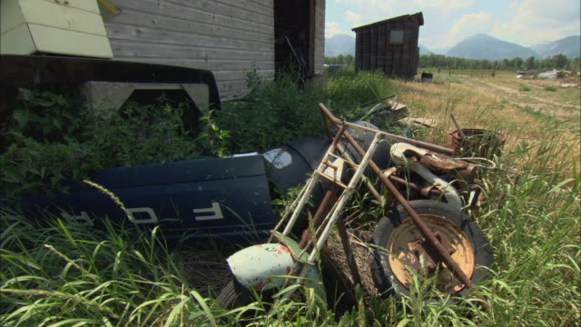 ms old car and motorcycle parts in field, wooden shed in background / stevensville, montana, usa - shed stock videos & royalty-free footage