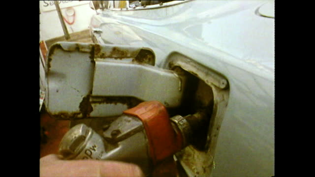 old car is refuelled and sets off on a journey in usa; 1972 - 以前の点の映像素材/bロール