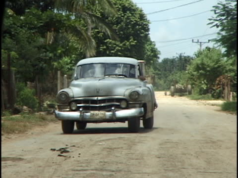 MS, Old car riding on dirt road, Havana, Cuba