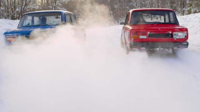 Old cars racing away through snow in rural area