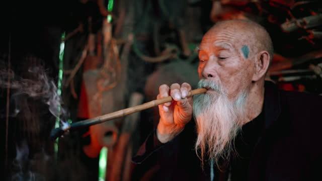 old chinese senior man lighting smoking pipe in simple wooden hut - wisdom stock videos & royalty-free footage