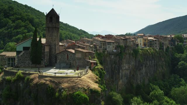 vecchia chiesa e case nella città catalana di castellfollit de la roca sulla scogliera - colpo di drone - roca video stock e b–roll