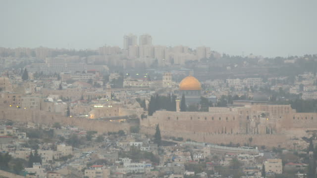 old city temple mount w/ dome of the rock shrine behind walls vehicles driving along streets lowrise buildings fg modern highrises bg fog smog... - conflitti arabo israeliani video stock e b–roll