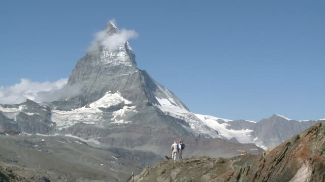 ws old couple tourist standing in front of matterhorn mountain / zermatt, valais, switzerland - distant stock videos and b-roll footage