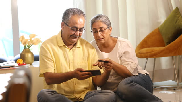 old couple using phone and credit card at home - husband stock videos & royalty-free footage