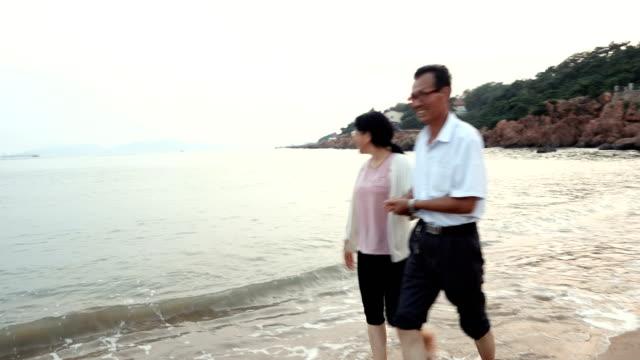 Old Couple walking at sea beach