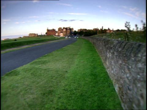 old course golf course, rock wall, paved pathway, flag on green, north sea in distance, royal & ancient golf club of st. andrews clubhouse &... - golf links stock videos & royalty-free footage