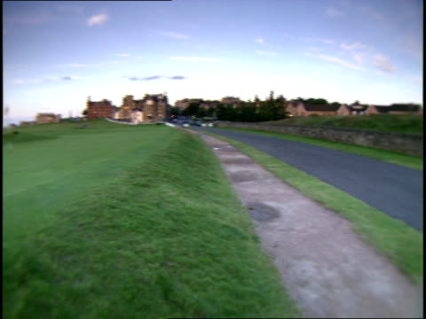 old course golf course rock wall paved pathway flag on green north sea in distance royal amp ancient golf club of st andrews clubhouse amp hamilton... - golf links stock videos and b-roll footage