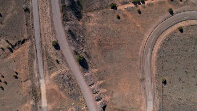 stockvideo's en b-roll-footage met oude vuile landweg in een woestijn dichtbij edgewood, new mexico. luchtdronevideo met de panning camerabeweging - sunny