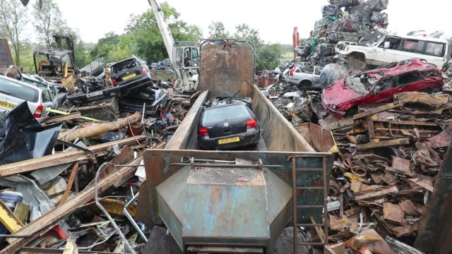A old endoflife scrap car is placed in a crusher as it is processed at Pylle Motor Spares and Metal Processing a licensed scrap yard in Pylle near...