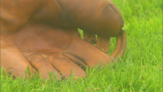 old era baseball field glove on grass of baseball field. major league baseball, mlb, old school, now and then, vintage, generation. - sports glove stock videos & royalty-free footage