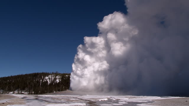 vídeos de stock, filmes e b-roll de old faithful erupting, yellowstone national park scenic in winter - 1 minuto ou mais