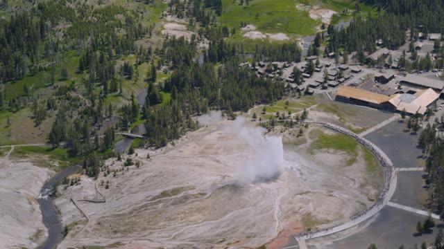 old faithful erupts near old faithful lodge at yellowstone national park. - old faithful geysir stock-videos und b-roll-filmmaterial