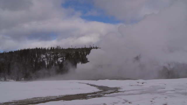 old faithful geyser emitting smoke surrounded by snow against sky, vapor erupting at national park during winter - yellowstone, wyoming - old faithful stock videos & royalty-free footage