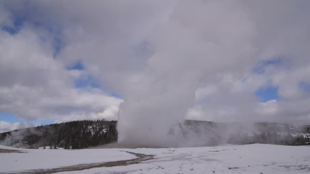 old faithful geyser emitting smoke surrounded by snow, vapor erupting at national park against cloudy sky during winter - yellowstone, wyoming - emitting stock videos & royalty-free footage