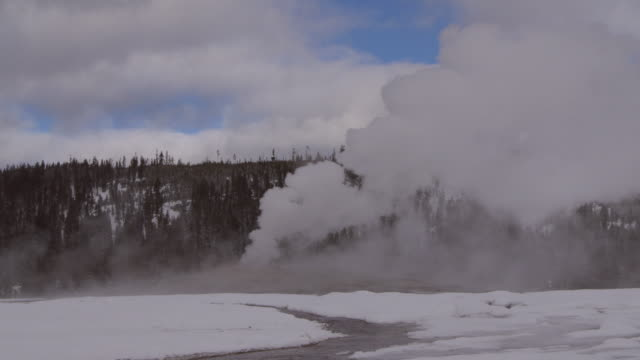 old faithful geyser erupting steam surrounded by snow against sky, vapor emitting at national park during winter - yellowstone, wyoming - old faithful stock videos & royalty-free footage