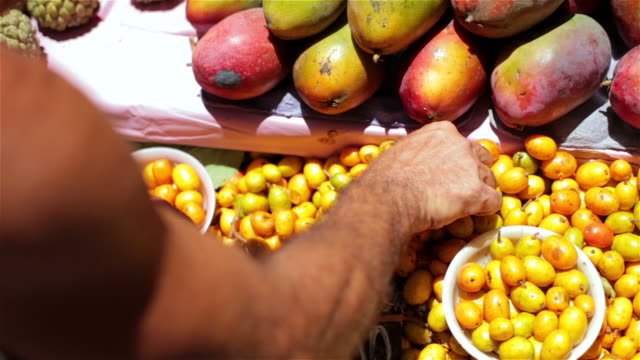 old farmer's hands arrange cajˆ fruit on display in brazilian market - multi coloured stock videos & royalty-free footage