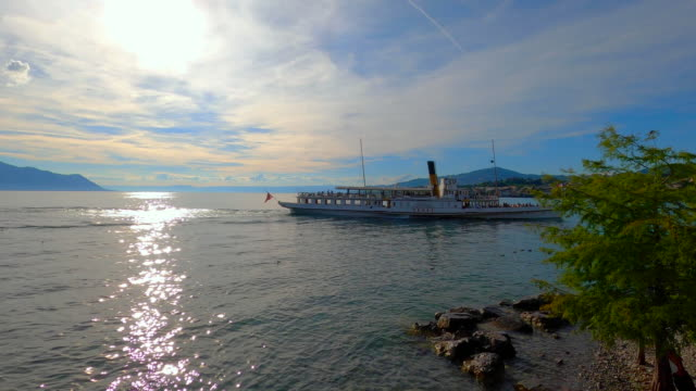 """old fashion paddle wheel passenger ferry """"vevey"""" arriving in montreux and doing scheduled trip along the swiss shores aswell as cruises on lake geneva and and makes stops in evian and thonon in france - montreux stock videos & royalty-free footage"""