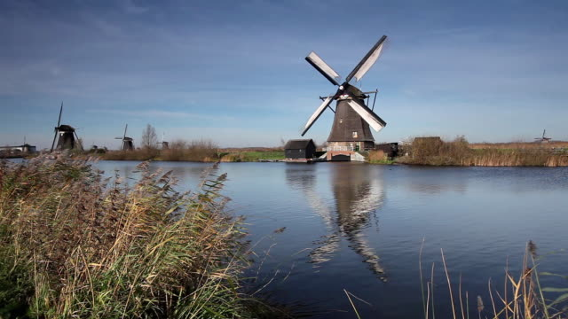 ws old fashion windmills by canal, grass blowing on wind in foreground / kinderdijk, holland, netherlands - mill stock videos and b-roll footage