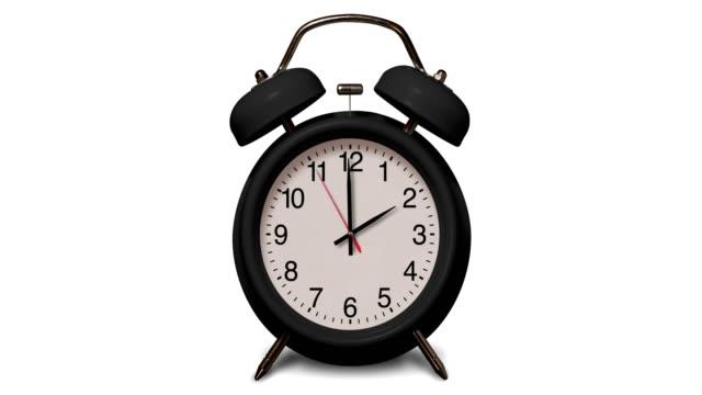 vidéos et rushes de le réveil noir démodé sonne à 2 o'clock sur le fond blanc - réveil