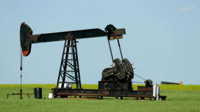 Old fashioned oil pump jack Kansas green agricultural fields