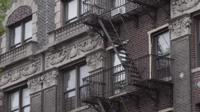 stockvideo's en b-roll-footage met old fire escape on the outside of a brooklyn apartment building. - establishing shot