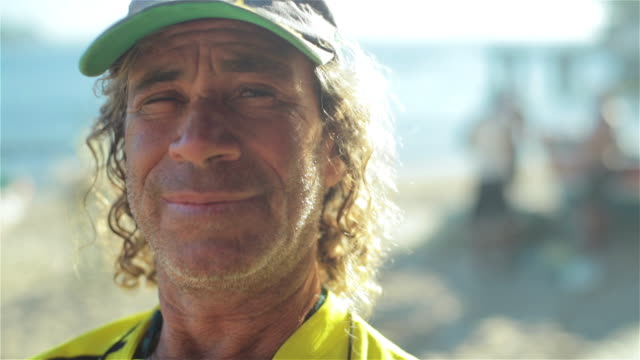 old fisherman in brazilian team colors smiles for camera on copacabana beach - fisherman stock videos & royalty-free footage