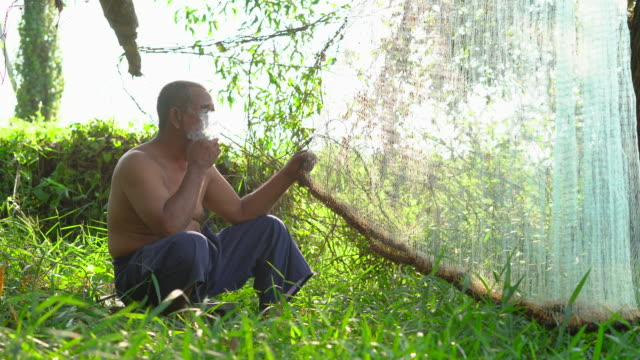 old fisherman smoking while checking fishing net - labour party stock videos & royalty-free footage