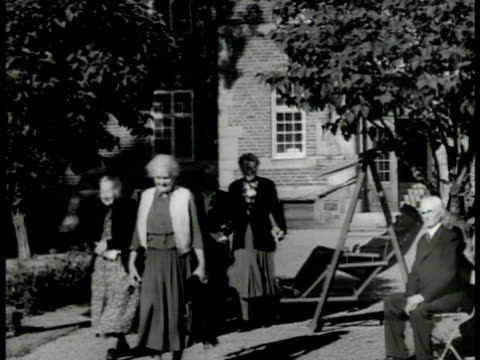 stockvideo's en b-roll-footage met old folks home ws elderly swedish people walking outside of home ext ms swedish pension headquarters sign int ms workers at check machines cu... - 1949